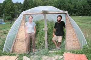 Two people standing in the entry to a hoop house